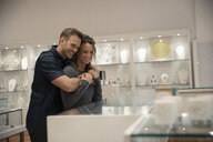 Affectionate couple shopping for jewelry at display case in boutique - HEROF12023