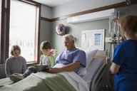 Grandfather and grandson using digital tablet in hospital - HEROF12074