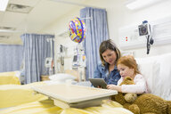 Mother and daughter using digital tablet in hospital - HEROF12080