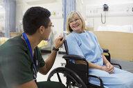 Male nurse talking to woman in hospital wheelchair - HEROF12086