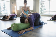 Instructor stretching womans back in restorative yoga class - HEROF12092