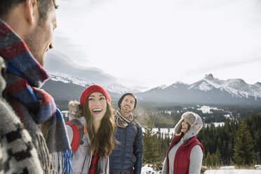 Friends laughing below snowy mountains - HEROF12155