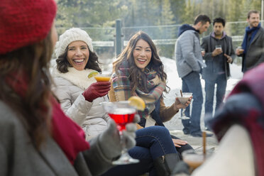 Friends in warm clothing drinking on patio - HEROF12167