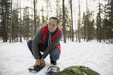 Man putting on snowshoes in snowy woods - HEROF12173