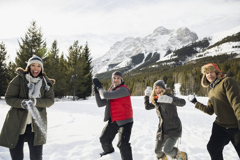 Friends enjoying snowball fight below snowy mountain - HEROF12194
