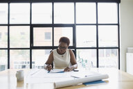 Female architect reviewing paperwork in conference room - HEROF12227