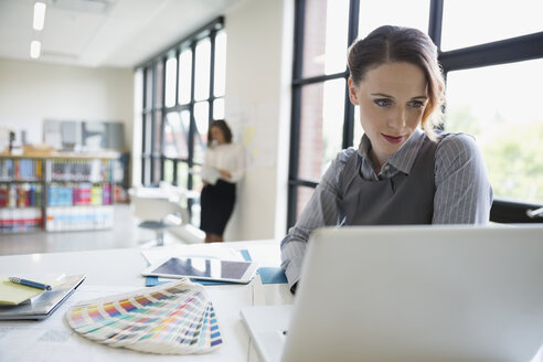 Female designer using laptop next to color swatches in office - HEROF12239