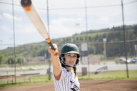Focused middle school girl softball player ready to bat - HEROF12260