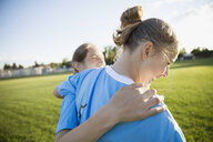 Laughing middle school girl soccer teammates hugging on sunny field - HEROF12266