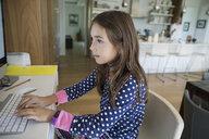 Girl in pajamas using computer at desk - HEROF12275