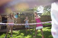 Girls spinning in plastic hoops in sunny backyard - HEROF12293
