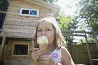 Girl eating melting messy ice cream cone in sunny backyard - HEROF12302