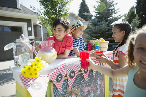 Girls buying lemonade from boys at lemonade stand in sunny driveway - HEROF12332