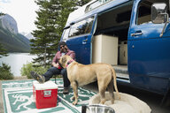 Man and dog relaxing outside camper van at remote lakeside - HEROF12335