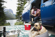 Man playing guitar at camper van near dog at remote lakeside - HEROF12338