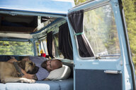 Man and dog relaxing in the back of camper van - HEROF12341