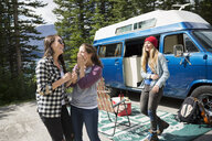 Female friends laughing outside camper van in woods - HEROF12344