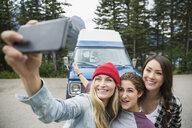 Female friends taking selfie with camera phone outside camper van - HEROF12347