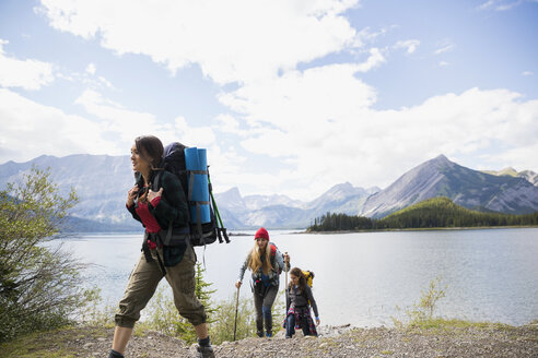 Female friends hiking with backpacks and hiking poles at remote mountain lakeside - HEROF12356