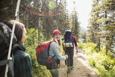 Friends hiking with backpacks and hiking poles on sunny remote trail in woods - HEROF12359