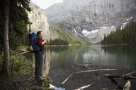 Male hiker with backpack enjoying tranquil, remote mountain lake view - HEROF12368