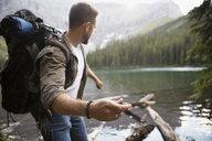 Man hiking skipping stones in lake - HEROF12374