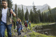 Friends hiking along lake on trail below mountains in remote woods - HEROF12377