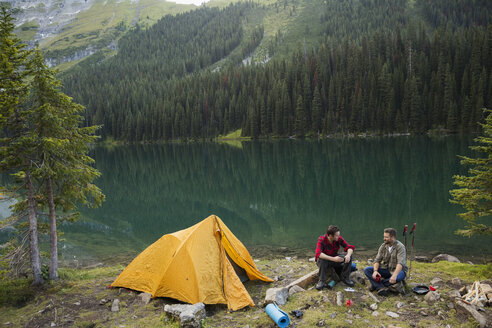 Male friends camping at remote lakeside campsite - HEROF12386