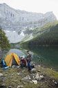 Male friends camping at remote mountain lakeside campsite - HEROF12389