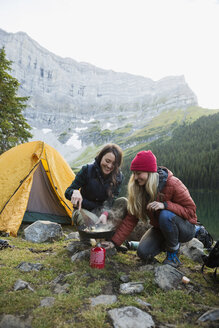 Female friends cooking with skillet over kerosene camping stove at remote campsite - HEROF12392
