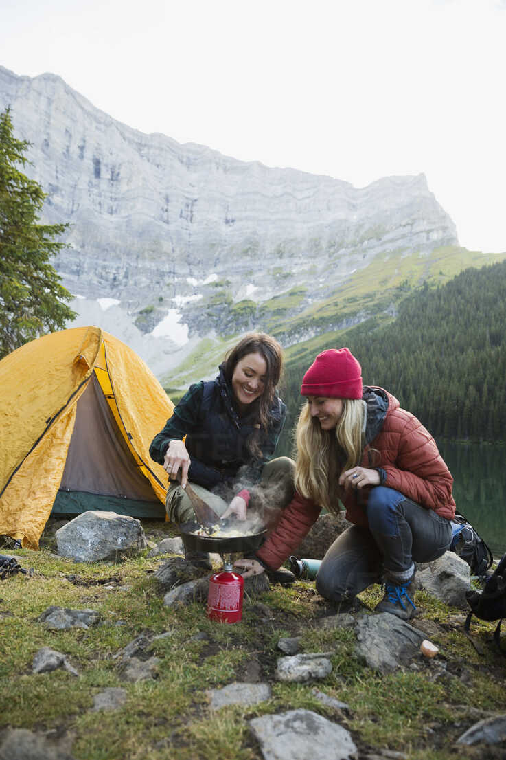 Female friends cooking with skillet over kerosene camping stove at remote campsite - HEROF12392 - Hero Images/Westend61