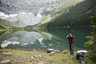 Male hiker using binoculars at remote mountain lakeside - HEROF12395