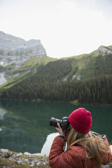 Female photographer photographing remote lake with digital camera - HEROF12398