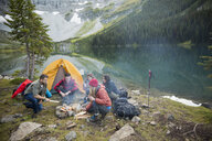 Friends hanging out around campfire at remote lakeside - HEROF12401