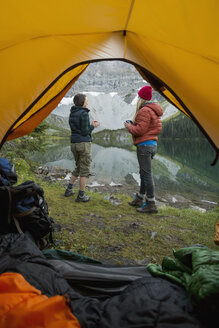 Female friends drinking coffee and talking at lakeside outside of camping tent - HEROF12404