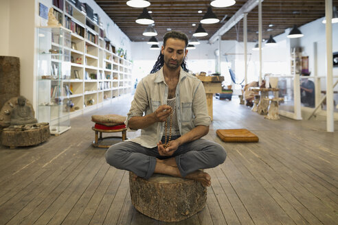 Man sitting in lotus position with prayer beads in new age shop - HEROF12410