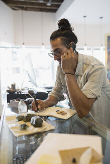 Male new age shop owner talking on cell phone behind counter with rocks and crystals - HEROF12413