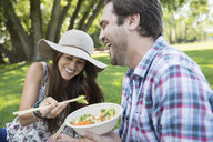 Laughing couple eating with chopsticks in park - HEROF12425