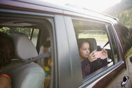 Girl using camera phone at window in back seat of SUV - HEROF12428