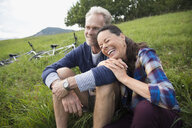 Laughing senior couple relaxing near mountain bikes in remote rural field - HEROF12434