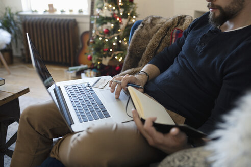 Young man with journal using laptop in Christmas living room - HEROF12470
