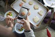 Young woman with camera phone photographing decorated Christmas sugar cookie - HEROF12473