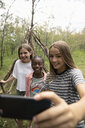 Tween girl friends taking selfie, making teepee in woods - HEROF12500