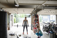 Young women friends working out, weightlifting in garage - HEROF12521