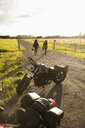 Women friends walking away from motorcycles on sunny rural road - HEROF12524