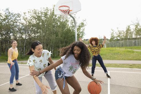 Teenage girl friends playing basketball at park basketball court - HEROF12527