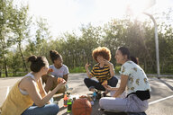 Teenage girl friends eating pizza on sunny park basketball court - HEROF12530