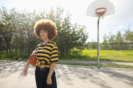 Portrait confident, cool teenage girl with afro playing basketball at park basketball court - HEROF12641