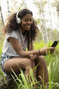 Smiling young woman with headphones listening to music with mp3 player in woods - HEROF12644
