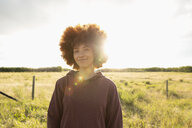 Portrait smiling, confident teenage girl in sunny rural field - HEROF12650